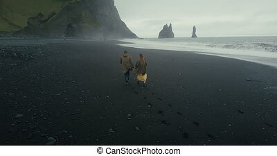 Aerial back view of the young hipster couple running on the black volcanic beach near the troll toes in Iceland.