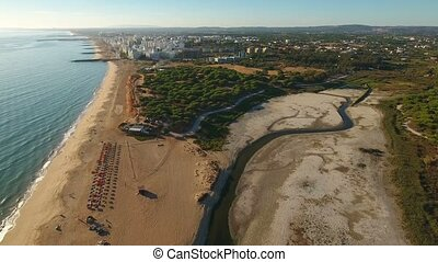 Aerial. Beach and lake parched, town of Quarteira, filmed...