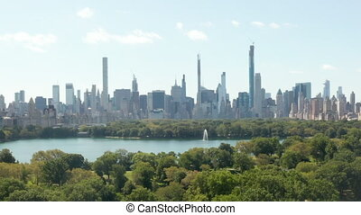 AERIAL: Beautiful Central Park view and Manhattan Skyline in Background at sunny summer day