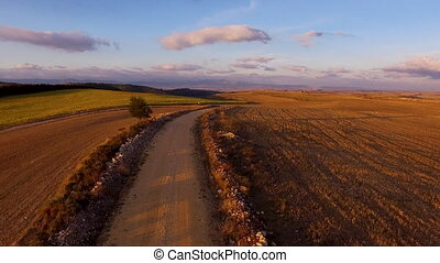 Aerial bird view footage flight over rural road in beautiful countryside landscape at sunset .