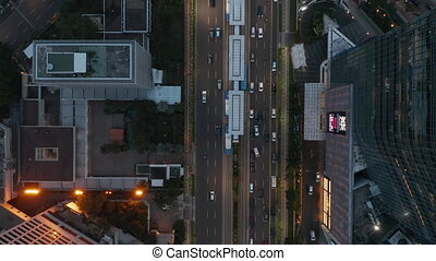 Aerial Birds Eye Overhead Top Down View closing in on busy car traffic and public transportation stop in busy multi lane road 4K