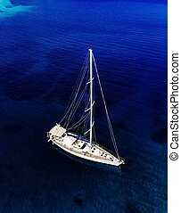 Aerial birds eye view from drone of yacht in deep blue sea
