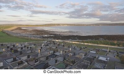 Aerial birds eye view of an Irish burial graveyard cemetery at evening sunset. Beautiful peaceful scenic Irish landscape in County Clare, Ireland