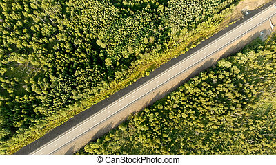 Aerial birds eye view over an empty country road between ...