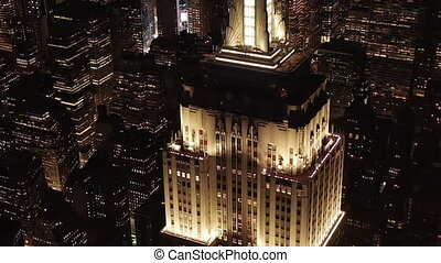 AERIAL: Breathtaking circle over the iconic Empire State Building above lit up parallel avenues and junctions residential condominiums and office buildings in Midtown Manhattan, New York City at night