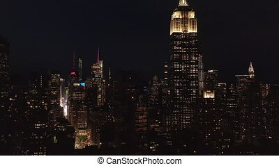 AERIAL: Breathtaking wide view the iconic Empire State Building disappearing behind residential condominiums and office buildings in Midtown Manhattan, New York City at night