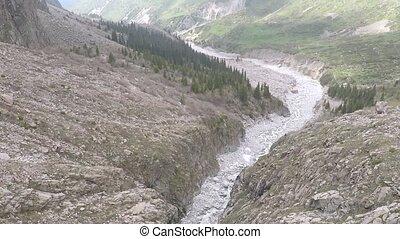 Aerial camera follows mountain stream on white rocks. High altitude shot
