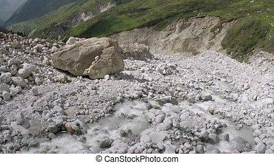 Aerial camera follows mountain stream on white rocks. Low altitude shot