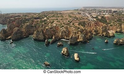 Aerial. Cape air video Ponta de Piedade, boat with tourists on the sea.