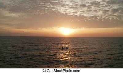 Aerial cinematic shot of sea with boat over beautiful sunset...