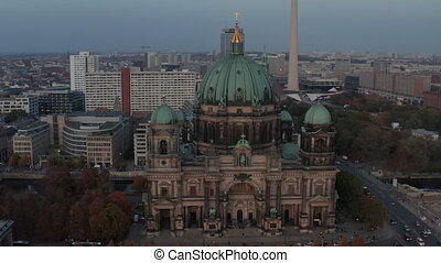 AERIAL: Circling Berlin Cathedral beautiful old structure in vibrant fall colors with golden cross on top and city life moving around