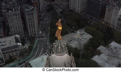 AERIAL: Circling golden statue in New York City with highway traffic and busy City