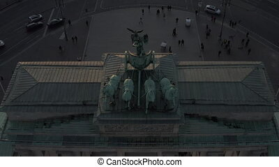 AERIAL: Close birds view on Quadriga Green Statue on Brandenburg Gate in Berlin, Germany with beautiful sunset sunlight 4K