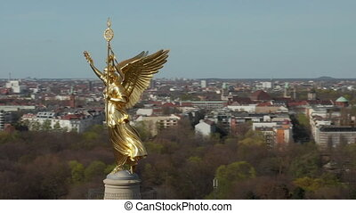 AERIAL: Close Up Circling around Berlin Victory Column Golden Statue Victoria in Beautiful Sunlight and Brandenburg Gate in Background HD