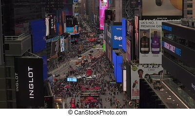 AERIAL: Close up flight over Times Square heart of New York City at Daylight with crowd of people and heavy car traffic