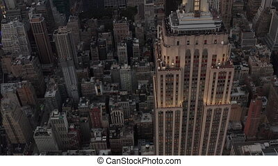 AERIAL: Close Up of Empire State building at dusk with lights on in beautiful 4K