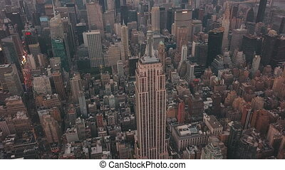 AERIAL: Close up of Empire State Building with Midtown Manhattan, Times Square in the background at Dawn, Sunset
