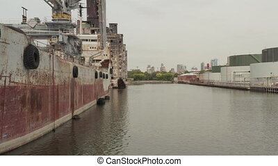 AERIAL: Close up of old Cargo Ship and Warehouse in the Docks of New York City on a cloudy Grey day