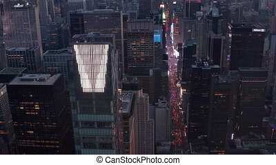 AERIAL: Close up view of new Manhattan Skyscraper with Times Square and City lights glowing in the back, Beautiful