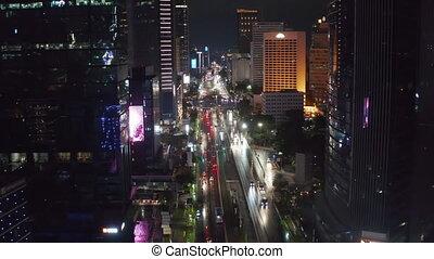 Aerial descending pedestal shot flying sideways of busy city multi lane traffic at night in city center of Jakarta