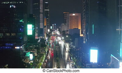 Aerial descending pedestal shot of night time traffic on a busy city highway surrounded by tall skyscrapers in Jakarta, Indonesia 4K