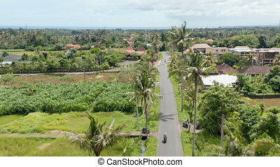 Aerial dolly shot following a motorcyclist driving on the road through the traditional residential neighborhood in Bali, Indonesia
