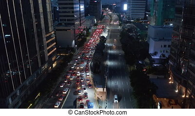 Aerial dolly shot of cars merging into a multi lane stopped traffic at a traffic light in urban city center 4K