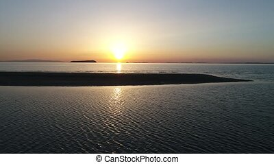 Aerial dolly view of calm ocean at sunset - aerial drone...