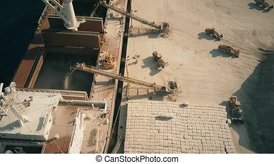 Aerial down shot of bulk carrier ship and cement loaders at...