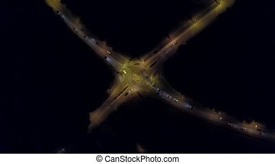 Aerial down view hyperlapse of a car road roundabout at night