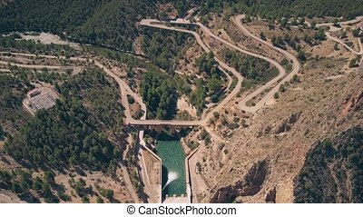 Aerial down view of windy hairpinned car road and dam in...