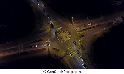 Aerial down view timelapse of a car road roundabout at night