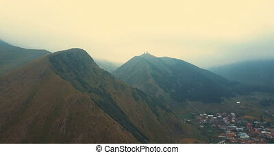 Aerial Drone Flight Over Mountain Range Through Clouds