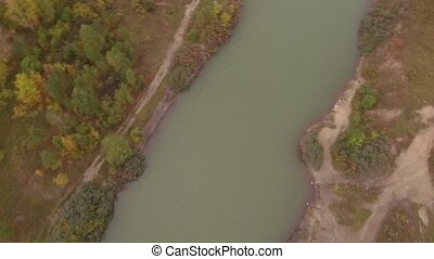 aerial drone flight over small lake. camera rotation.