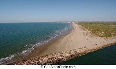 Aerial. Drone flight over the breakwater overlooking the Monte Gordo. Vila Real Santo Antonio