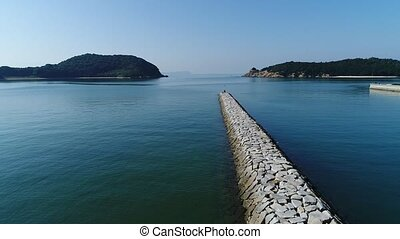 aerial drone flying, breakwater of stone in the sea - aerial...