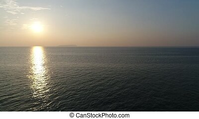 aerial drone flying, dolly in of calm, evening sea - aerial...