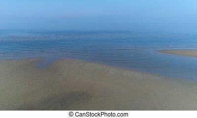 aerial drone flying, dolly in of calm, sea shallow - aerial...