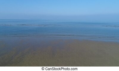 aerial drone flying, dolly in of calm, sea shallow sandy -...