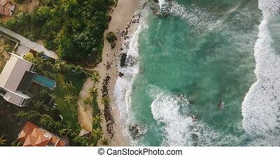 Aerial drone flyover shot of idyllic ocean coastline,...