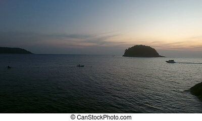 Aerial drone footage of flight above calm water, near wild island and yacht driving in sunset soft ligh
