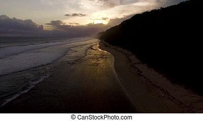 Aerial drone footage of ocean waves breaking before the...