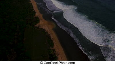 Aerial drone footage of ocean waves breaking before the...