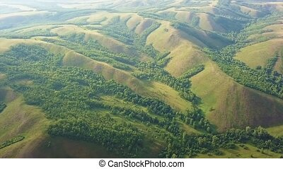 Aerial Drone Footage View: Flying over spring mountains, hills and meadows with pine forests in sun soft light. Fly out. Carpathian Mountains, Romania, Europe. Beautiful landscape.