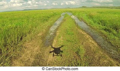 Aerial drone landing at the grass road in steppe of...