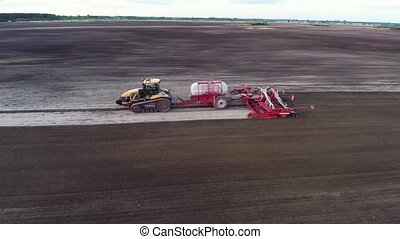 Aerial drone shot of a combine harvester working in a field at sunset