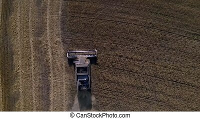 Aerial drone shot of a combine harvester working in a field, Shot in 4K