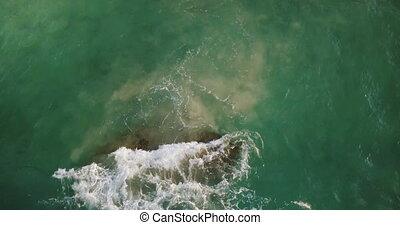 Aerial drone shot of beautiful green ocean wave crashing over a cay reef stone near shore, creating beautiful white foam
