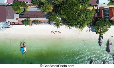 Aerial drone shot of word ZUMBA made up of women on the sandy beach