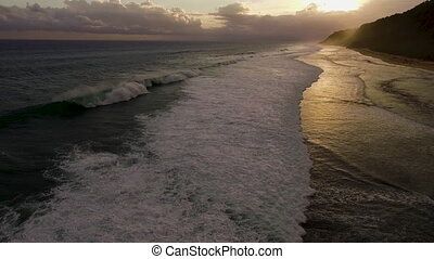 Aerial drone slow motion footage of ocean waves on sunset....